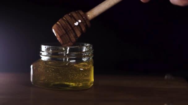 Do sklenice se z medu vylívá med. Close-up. Silné odplení medu