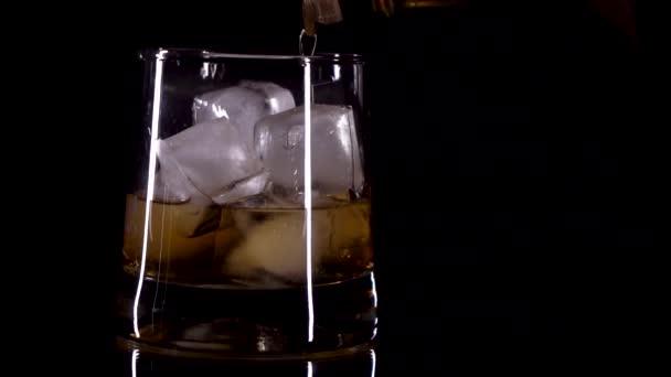 whiskey se nalije do skleničky s ledem na černém pozadí