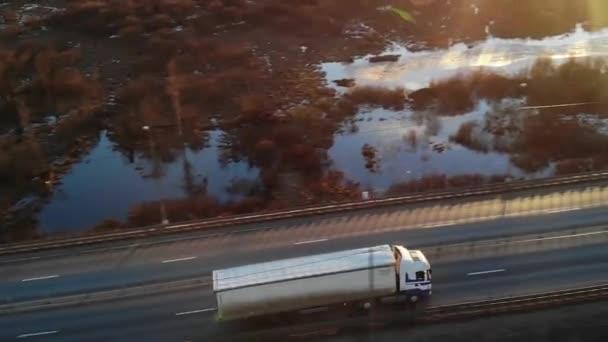 Auto e camion semi merci carichi di merci che guidano lungo unautostrada vuota.