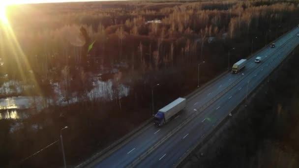 Automobily a nákladní polovozy naložené zbožím, které jede po prázdné dálnici a přepravují náklad v ranním rozbřesku. Nákladní cisterna dodávající náklad při zlatém západu slunce.