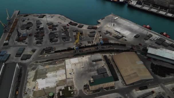 Madártávlati panoráma a rakománykikötőre, több száz export- és importrakományt szállító hajóval és több ezer konténerrel a kikötőben.