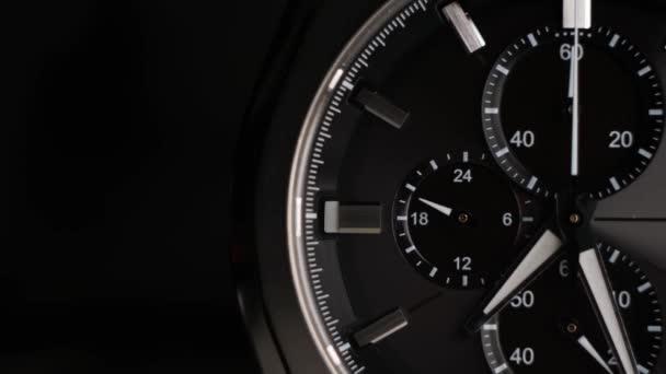 Wrist Watch idő telik közelről egy fekete háttér. fehér órakezek