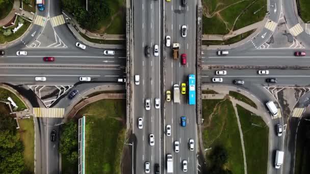 Pohled na městskou křižovatku s autobusy, auty, náklaďáky. Provoz ve dne, v Megapoli. Jít dál s auty.