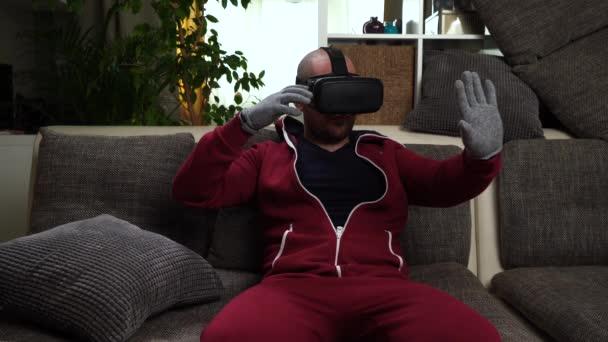 bärtiger Mann in rotem Overall spielen VR oder Virtual-Reality-Brille Spiel.