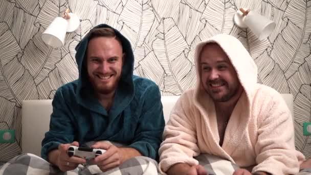 Két fickó számítógépes játékokat játszani az ágyon fürdőköpeny és nyerj. Lassú mozgás Footage 2 szakállas férfiak Play videojáték