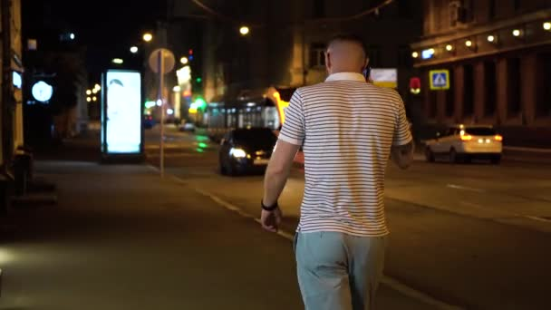 Bearded man in striped white and black t shirt and green shorts walking on the street at night and talk by mobile phone or cellphone