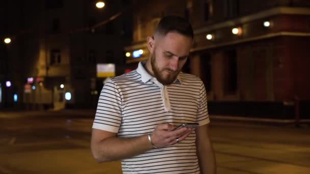Hezký vousatý muž chůze na noční ulici a používání mobilního telefonu. Užijte si noční procházku.