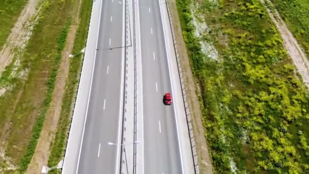 Aerial view of a red retro car drive on road or highway in the middle of the day. Not a lot of cars on motorway. High angle shot.
