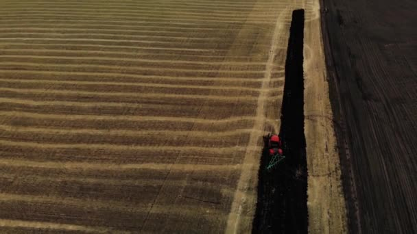 Tractor plowing fields, preparing land for sowing. Red tractor. Aerial view. Farmer in tractor preparing land in farmlands. Tractor plows a field. Agriculture industry.