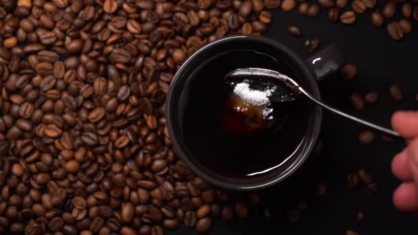 Person put sugar in black cup of black coffee and stirring coffee with a spoon. A lot of coffee beans on a black table. Slow motion.