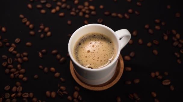 Pohled na míchací kávu v bílém šálku se lžičkou na černém stolku s kávovou fazolí na stole.