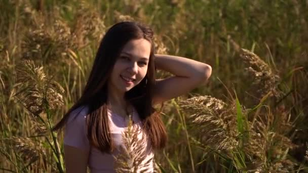 Attractive portrait of young girl in pink t-shirt in field looking in camera. Out of focus and then in focus. Slow motion footage.