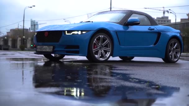 Moscow, Russia - 10 12 2019: russian model car roadster crimea blue color on the street. Footage of a sport car rainy day
