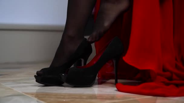 The girl in the bedroom in a red dress helps to put on black high-heeled shoes.