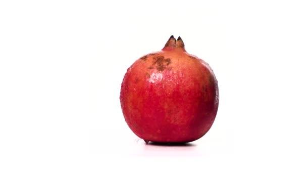Zralé červené granátové jablko v kapkách vody se otáčí na bílém pozadí izolátu. Nádherná exotická bobule. Ovocné granátové jablko obsahuje mnoho vitamínů a je antioxidant pro zdravé a silné lidi.