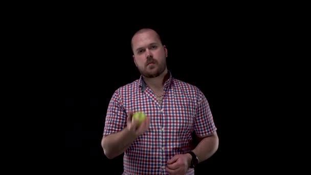 Vousatý a plešatý chlap v kostkované červenomodré košili na černém izolovaném pozadí jíst zelené jablko. Zdravý životní styl - jíst zeleninu a ovoce.