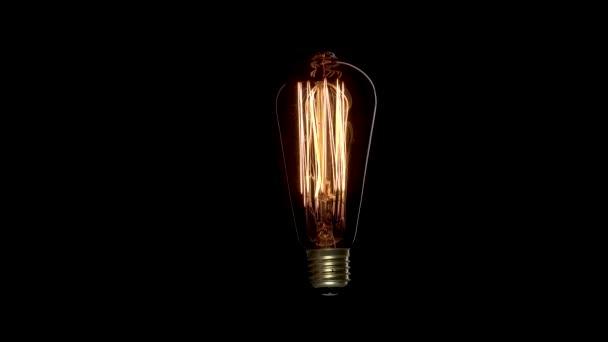 Edisonova lampa bliká na černém pozadí. Jantar wolfram barva staré retro lampy zapnout a vypnout s drátem.
