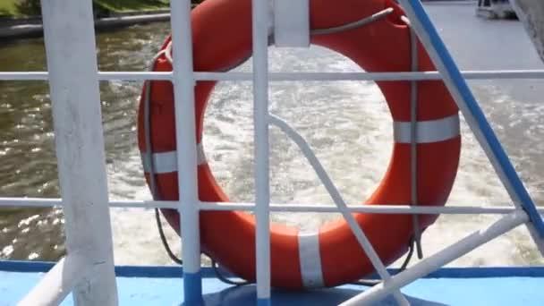 Rettungsring, der an einem sonnigen Tag an der Reling des Schiffes hängt. Wind weht Flagge von Russland dahinter, Wellen von Wasser im Hintergrund.