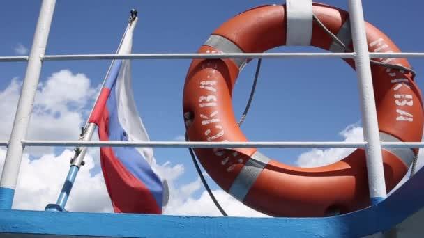 Rettungsring mit der Aufschrift Moskau, der an einem klaren, sonnigen Tag an der Reling des Schiffes hängt. Wind weht Flagge Russlands, weiße Wolken am blauen Himmel im Hintergrund. Fahrt mit dem Wassertransport, Bootsfahrt auf dem Fluss