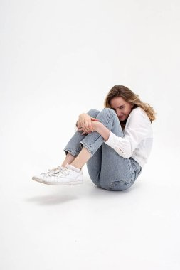 Portrait of young smiling caucasian woman posing in shirt, blue jeans, sitting on white studio background holding knees. model tests of pretty girl in basic clothes. attractive female poses, smiles stock vector