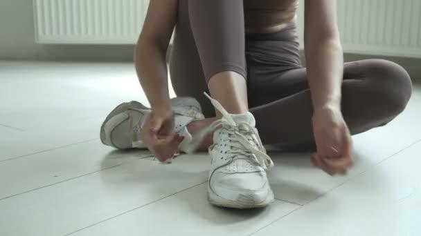 young girl in sportswear sits on floor on knees, untying shoelaces on sneakers