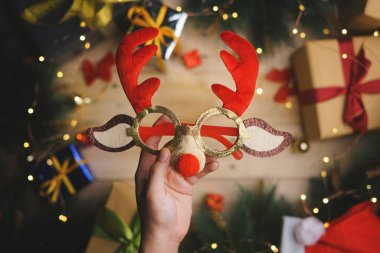 Hand Holding Christmas Reindeer Glasses Above Christmas Decoration. Top View