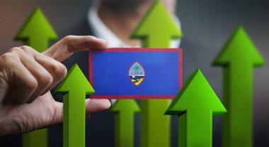 """Картина, постер, плакат, фотообои """"Нации концепции роста, зеленые стрелки - бизнесмен, держа карты флага Гуама вверх"""", артикул 229665248"""