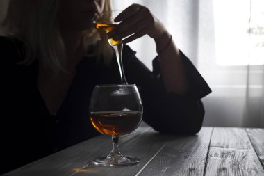 woman drinking cocktail with whiskey glass on table