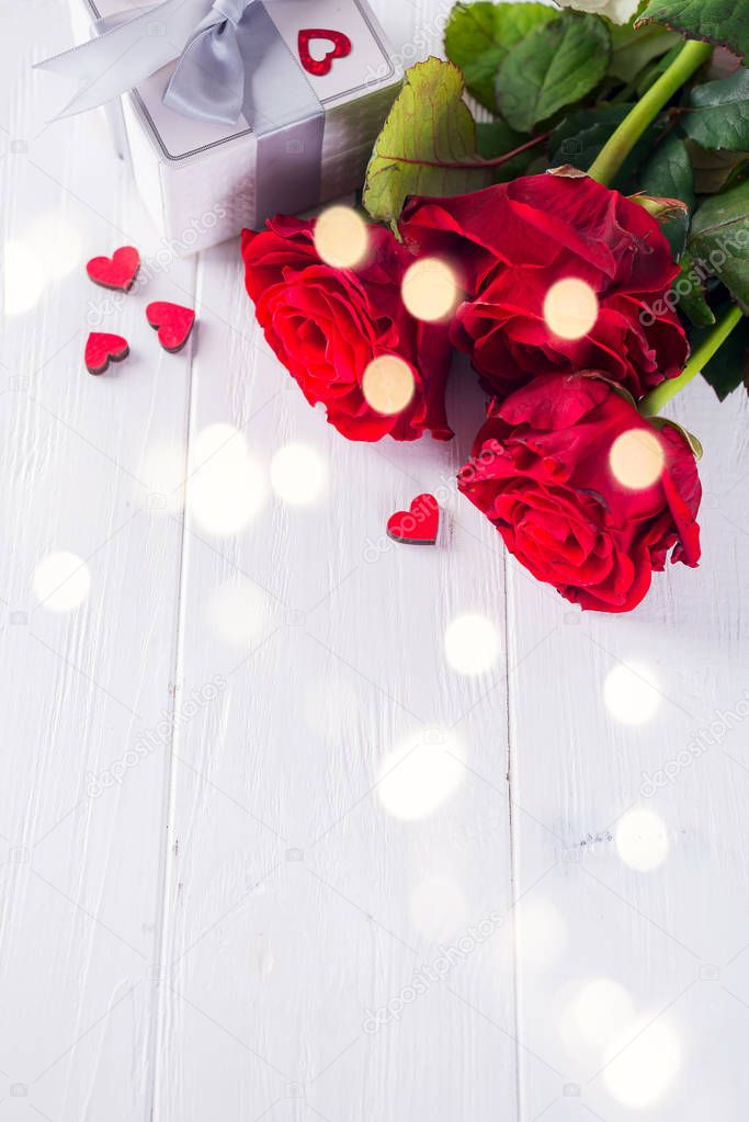 Valentines Chocolate-Love sweet heart shaped with gift box on a white wooden background with red roses