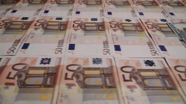 Řádky 50 eurobankovek s bankovkami o 100 dolaru uprostřed.