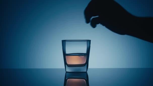 Sklenice whisky na reflexním povrchu na modrém pozadí