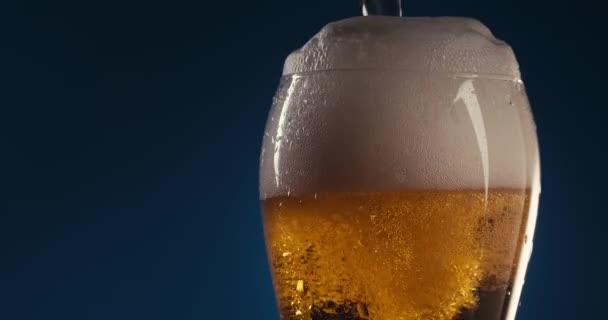 Túltöltés egy pohár sört. Kék háttér