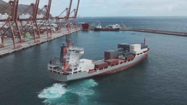 Nákladní loď s kontejnery vplouvá do přístavu za účelem vykládky.