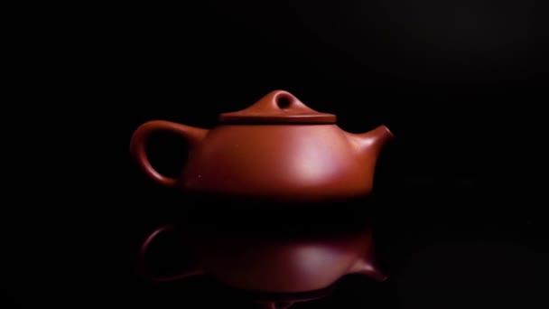 Hnědá hliněná čínská Čajová konvice pro slavnostní čaj na černém pozadí. Elegantní červenohnědý čajník. Zrcadlí odraz s přiblížením. Hliněný čajník. Krásná a elegantní. Luxusní stolní nádobí.