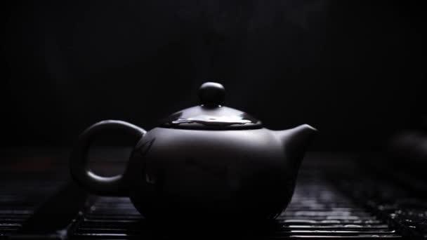 Čajník se dušený z čínského zeleného čaje. Horký hliněný čajník s párou na černém pozadí. Pomalé emoce. Kapky vody. Zalévání čínského rituálu. Asijská kultura. Nádherná luxusní konvice. Fascinující proces. Vyryté do elegantního nádobí.