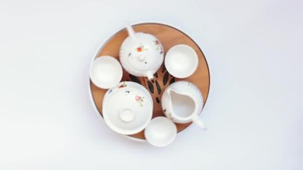 Kulatý čínský čajový stůl s pokrmy v rotaci. Zase nádobí. Na bílém pozadí krásná jídla