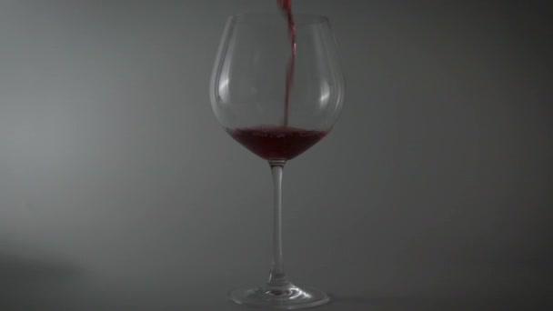 Rotwein in ein Glas auf hellem Hintergrund gießen. dünnstieliges Weinglas