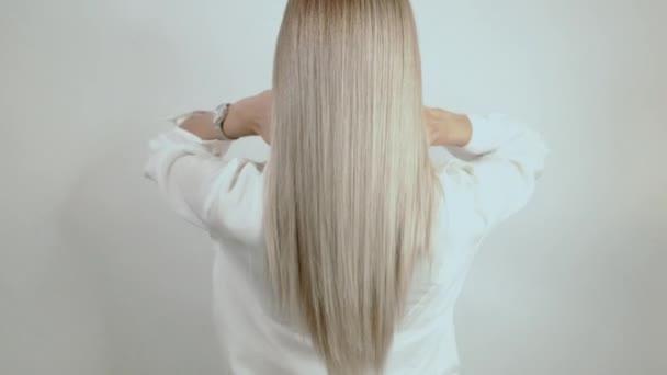 Dobře---Blondýnka, dlouhé vlasy se rozpadly na bílém pozadí. Reklama na vlasy. Krásný blonďatý pohled zezadu. Vlasy po kadeřnictví