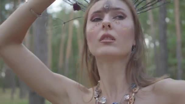 Portrét atraktivní dryáda nebo lesní víly s věnec větví na hlavě tančící pod stromy. Starodávný rituál lesní bytosti. Výkon tanečníka v lese