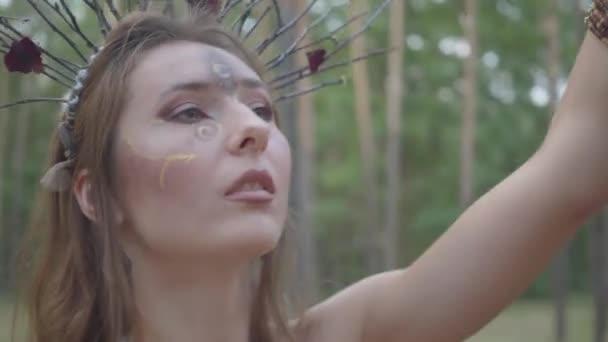 Portré vonzó Driád vagy erdei tündér a koszorú ágak a fejét táncolt a fák alatt. Az ősi rituális erdei lény. Az erdei táncosnő teljesítménye