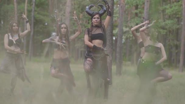 Csoport női táncosok a make-up és a misztikus mesés jelmezek táncoló Groovy tánc színes füst. Erdei tündérek, driádok szórakozni a fák között. A szabadtéri táncosok teljesítménye.