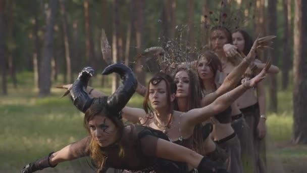 Csoport női táncosok a make-up és a misztikus mesés jelmezek táncoló Groovy tánc színes füst. Erdei tündérek, driádok szórakozni a fák között. Teljesítménye táncosok szabadban. Lassított mozgás