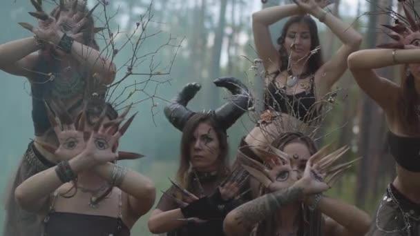 Dryády nebo lesní víly s malovanými oči na dlaních a falešné drápy pohybující se prsty s dlouhými drápy v oblaku kouře. Představení tanečníků v lese. Zpomaleně.