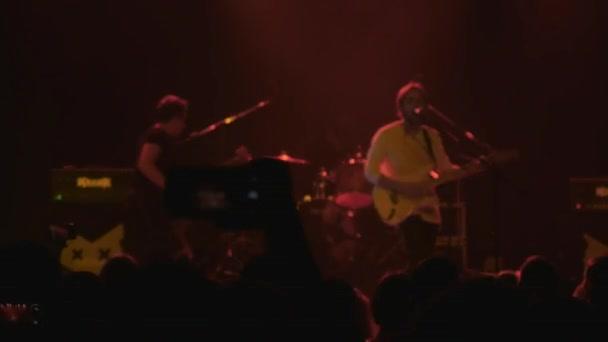 osoba z davu nahrává pořad na mobilním telefonu, zatímco hudebníci hrají na scéně, video