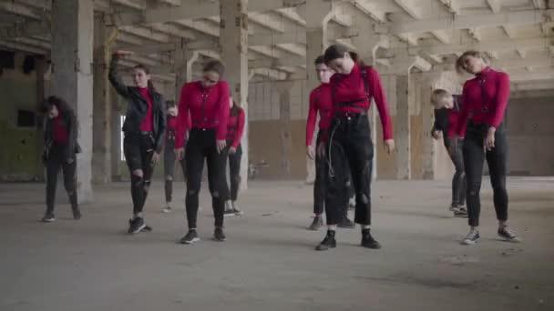 Ballerini di abilità professionali ragazze e ragazzi godendo mosse hip hop eseguendo danza freestyle insieme in un edificio abbandonato. Band caucasica fanno ballare moderno freestyle al chiuso. Fotocamera dal vivo.