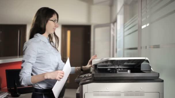 Mädchen kommt zum Drucker. junges Mädchen legt das Papier in den Drucker und druckt mehrere Exemplare aus. Mädchen schaut in die Kamera und lächelt.