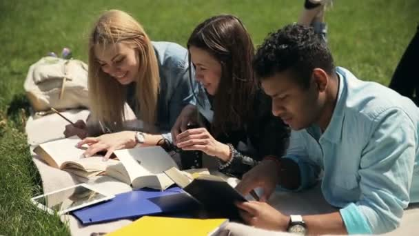 video of three students lying down on  blanket on green grass lawn with books and digital tablet, learning hometask concept