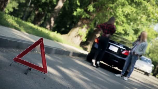 Vorne rotes Not-Stopp-Schild auf der Straße, im Hintergrund stehen verschwommene junge Frauen vor kaputtem Auto mit Not-Stopp-Signal.