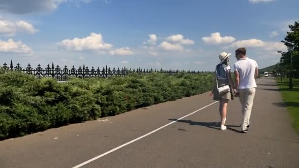 Mladý pár kráčí po cestě poblíž parku. Pár se drží za ruce a líbají.