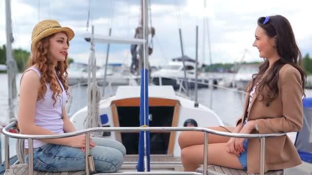 A lányok a jachton ülnek és beszélgetnek. A lányok mosolyognak. A lányok boldogok..